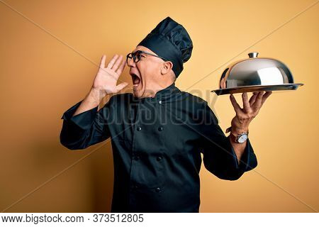 Middle age handsome grey-haired waiter man wearing cooker uniform and hat holding tray shouting and screaming loud to side with hand on mouth. Communication concept.