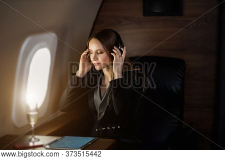 Happy Caucasian Young Blonde Woman In Stylish Black Dress Relaxing During Flight In Private Jet, Lis