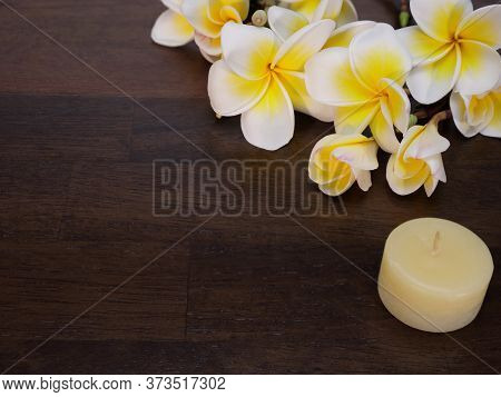 A Bouquet Of Beautiful Creamy White And Yellow Blooming Tropical Flowers And A Small White Candle On