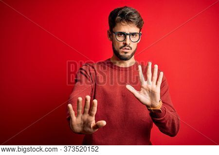 Young handsome man with beard wearing glasses and sweater standing over red background Moving away hands palms showing refusal and denial with afraid and disgusting expression. Stop and forbidden.