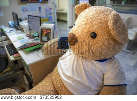 A Cute Live Size Stuffed Toy Bear Sitting The Clinic Screening Area Having Blood Pressure Measured.
