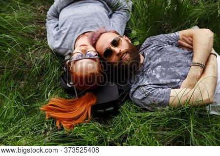 Cheerful Couple, Seated Down On A Green Grass, Seated Down In Sunglasses, Looking At Camera. Lifesty