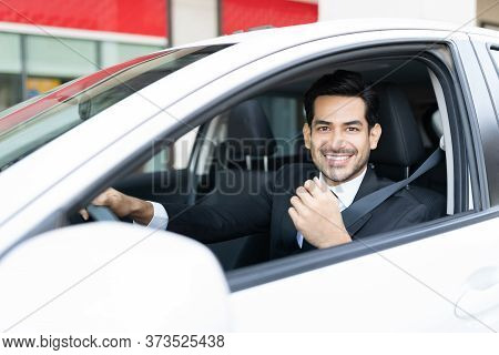 Smiling Hispanic Young Businessman Driving Car In City