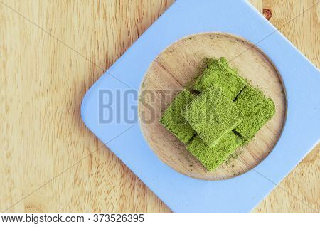 White Chocolate Fudge Heavily Coated With Fine Green Tea Powder. Brown Wooden Background.