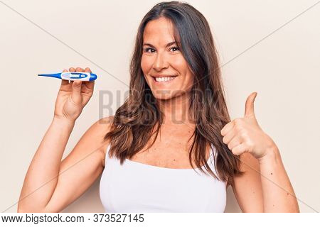 Beautiful brunette woman controlling temperature holding thermometer over white background smiling happy and positive, thumb up doing excellent and approval sign