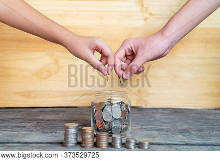 Help Save Money For The Future. The Two Hands Drop The Coin Into The Savings Glass, Close Up Hand Pu