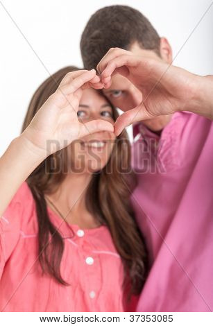 Young couple forming a heart shape with their hands