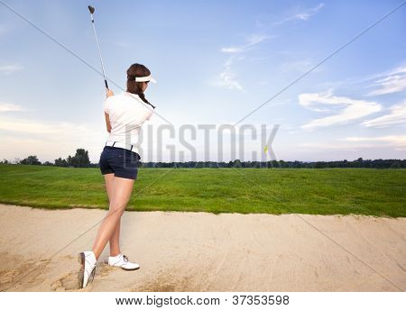 Woman golfer chipping golf ball out of sand trap onto green.