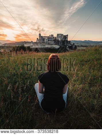 Beautiful Scenic View Of Castle Beckov In Europe - Slovakia With Woman Sitting On The Ground - Back