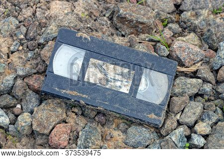 One Black Dirty Old Plastic Video Cassette Lies On Gray Stones And Rubble On The Street