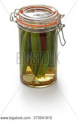 homemade pickled okra in jar isolated on white background
