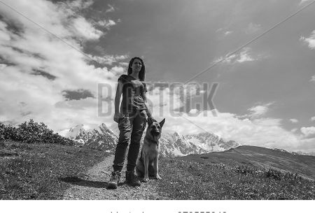 A Female Traveler And Her Friend A German Shepherd In The Mountains. Mountains Of Georgia, Svaneti.