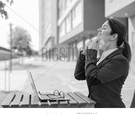 Happy Girl In A Suit Works Remotely On A Laptop Outdoors. A Business Woman Enjoys Pulling Off A Medi