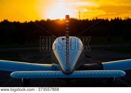 Quadruple Aircraft Parked At A Private Airfield. Rear View Of A Plane With A Propeller On A Sunset B