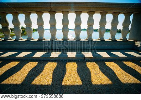 Old Stone Balustrade Of Railing Architectural Detail In Stone Back-lit Throwing Shadows Over Path