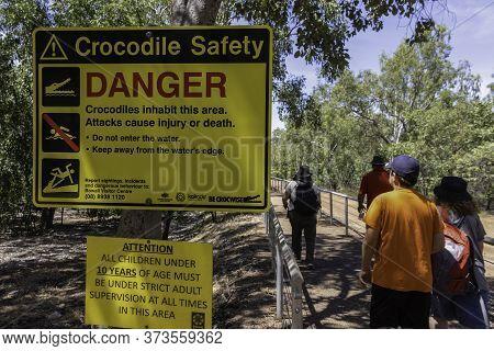 Kakadu National Park, Australia - March 12th, 2020: Tourists Walking Next To A Crocodile Safety Warn