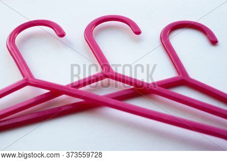 Pink Plastic Hangers For Adults And Childrens Clothing On White Background. The Concept Of Shopping,