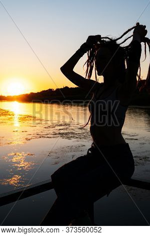Silhouette Of A Slender Girl With Dreadlocks On The River Bank In The Setting Sun