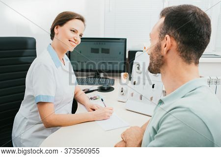 Consultation, An Audiologist Communicates With An Adult Man In A Hearing Clinic. Doctor And Patient,