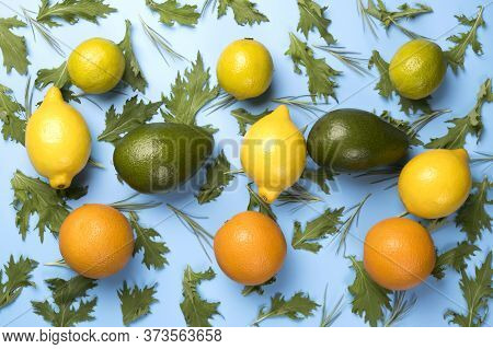 Close Up Of Citrus Fruits Orange, Lime, Avocado And Lemon On Green Rucola Salad Leaves Pattern On Bl
