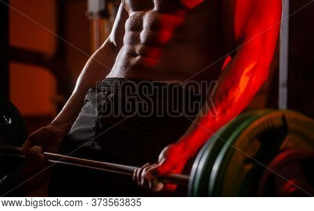 Man Lifting Barbells Working Out In Gym. Workout At The Gym. Athletic Man With Six Pack, Perfect Abs