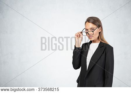 Portrait Of Beautiful Young European Businesswoman With Long Fair Hair Taking Off Her Glasses Near C