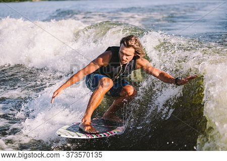 A Man Is Surfing On A Surfboard Drawn By A Motor Boat Above The Wave Of The Boat. Weixerfer Is Engag