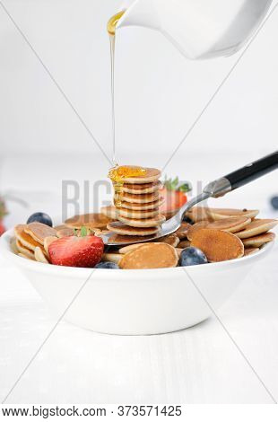 Tasty Breakfast With Mini Pancake Cereal With Strawberries And Blueberries.mini Pancake Cereal Is Ne