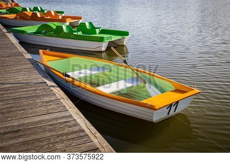Green-orange Boats And Pedal Boats In A Pond By A Pier