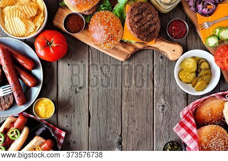 Summer Bbq Food Frame With Hot Dog And Hamburger Buffet. Above View Table Scene Over A Dark Wood Bac
