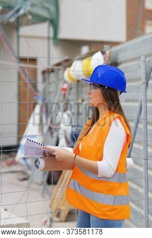 Architecture Student Holding Blueprints Checks A Construction Site