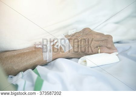 Senior Elder Asian Patient Woman In Hospital Eating Her Lunch On A Tray, Focus On Hand With Syringe