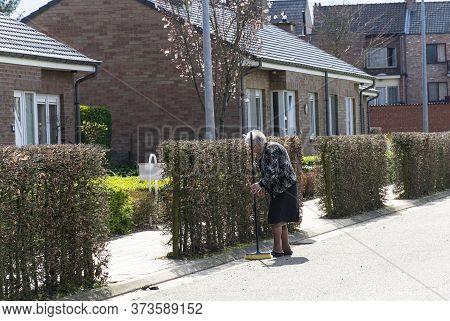Sint Gillis Waas, Belgium, March 18, 2020, Old Woman Sweeps Her Sidewalk With A Broom
