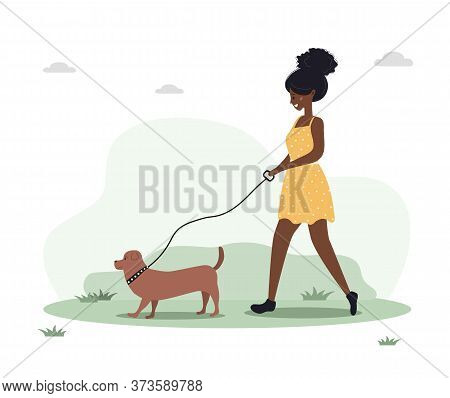 Young African Woman Walks With Dog Through The Woods. Concept Happy Girl In Yellow Dress With Dachsh