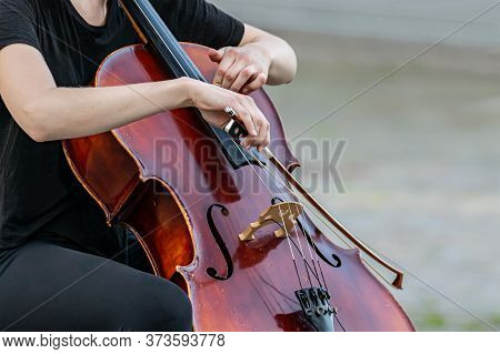 Woman Playing A Double Bass During A Performance Or Music Recital. Closeup Hands, The Instrument And