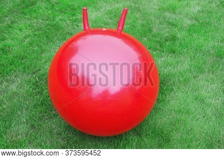 Red Round Rubber Big Fitball Fitness Ball With Horns Handles Red On A Green Lawn