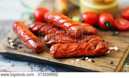 Appetizing Fried Smoked Sausages On A Wooden Board. Sausages With Spices And Mustard. German Appetiz