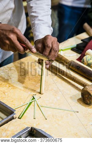 Papyerus artisan in Syracuse cutting the stem of a papyrus plant to obtain thin strips. Luxor, Egipt.