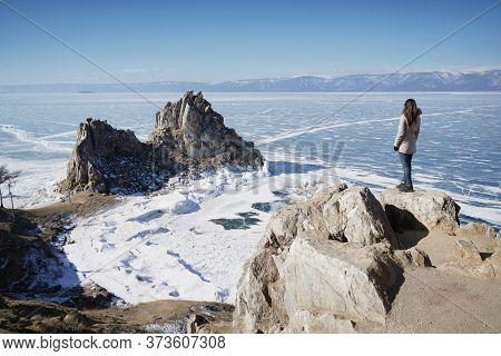 Lake Baikal At Winter. Woman Standing On A Cliff And Looking At Burkhan Cape And Shaman Rock. Deepes