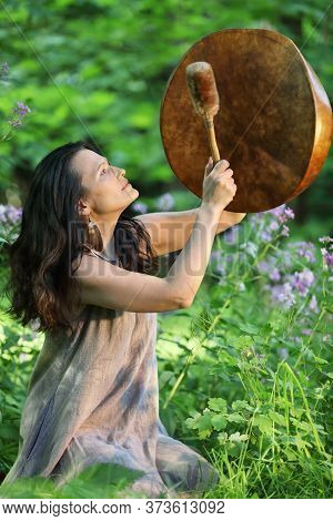 Shaman Woman Playing Her Shaman Sacred Drum In The Forest On Background With Leaves And Flowers. Eth