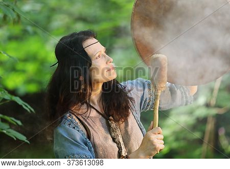Woman Dressed In Shaman Costume Playing On Shaman Frame Drum In The Nature