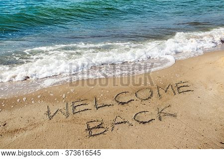 Words Welcome Back Are Written In The Sand On The Beach Near The Water, Reopen After The Coronavirus