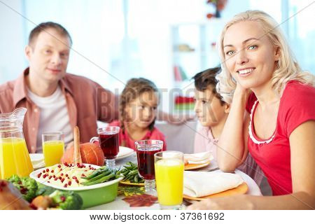 Portrait of happy woman sitting at festive table and looking at camera with her family on background