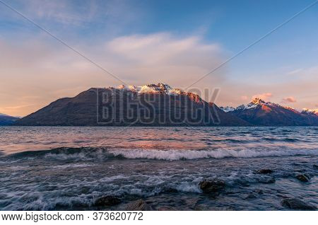 Winter Mountain Landscape With Icy Lake And Snow-capped Mountains. Winter Sunrise Landscape Of Lake