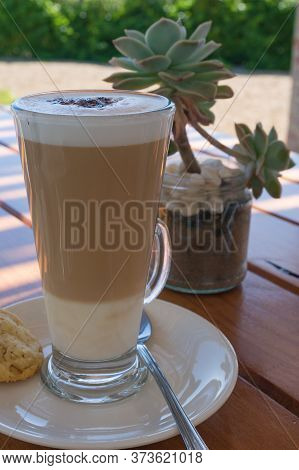 Coffee Drink In A Tall Clear Glass. Flat White Or Latte Coffee Art Served Outdoors In A Glass With C