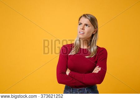 Perplexed Young Blonde Woman In Casual Clothes Posing Isolated On Yellow Orange Background In Studio