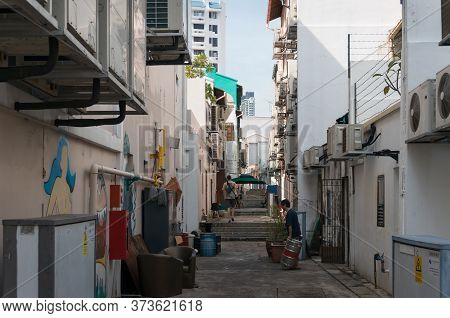 Singapore, Singapore - December 23, 2015: Backstreet In Singapore With People Doing Their Business.