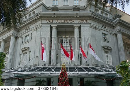 Singapore, Singapore - December 23, 2015: Fullerton Hotel Facade With Singapore Flags On The Front