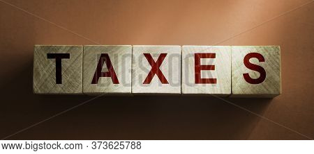 Tax Esword On Wooden Cubic Blocks On Beige Brown Background. Taxes And Fees Financial Concept