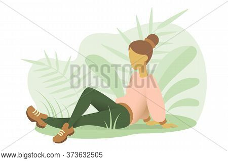 A Young Woman Sits On The Grass In The Park In A Relaxed Pose. A Girl Rests In Nature.sitting On The